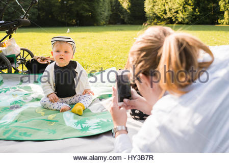 Sweden, Skane, Malmo, Mother photographing son (18-23 months) in park - Stock Photo