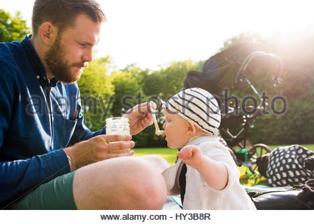Sweden, Skane, Malmo, Father feeding son (18-23 months) in park - Stock Photo