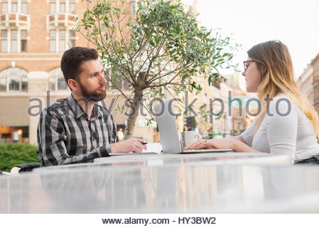 Sweden, Skane, Malmo, Two young people talking at sidewalk cafe - Stock Photo