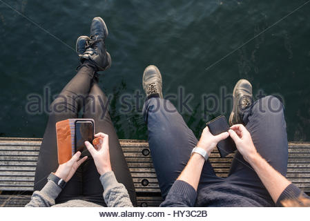 Sweden, Skane, Malmo, Overhead view of young man and woman sitting on pier with smart phones - Stock Photo