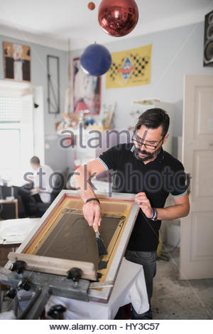 Portugal, Mature man doing screen printing - Stock Photo