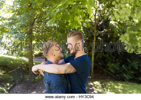 Norway, Oslo, Couple embracing in park - Stock Photo