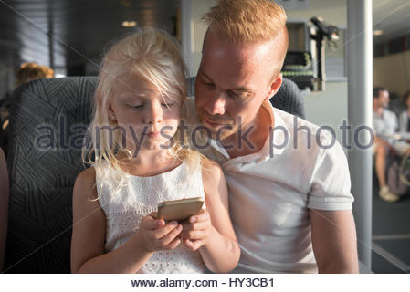 Sweden, Girl (6-7) and father using cell phone in ship cabin - Stock Photo