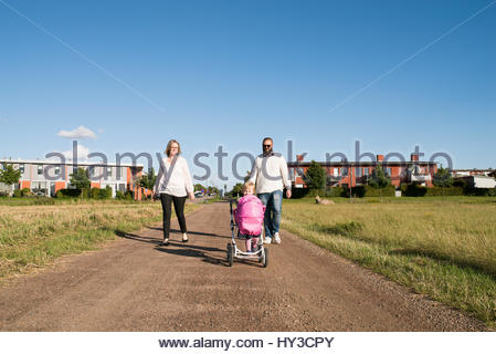 Sweden, Parents and daughter (2-3) walking in rural setting - Stock Photo