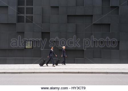 Norway, Oslo, Stewardesses walking with suitcases - Stock Photo