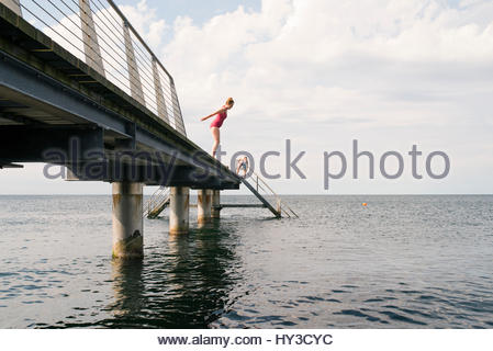 Sweden, Skane, Malmo, Woman jumping into water from pier - Stock Photo