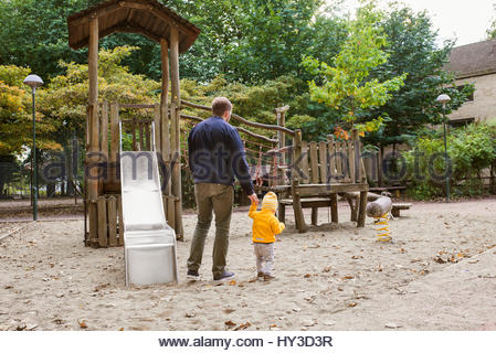 Sweden, Skane, Malmo, Father walking with son ( 12-17 months) next to slide in playground - Stock Photo