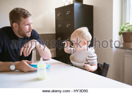 Sweden, Father sitting with son (12-17 months) at table - Stock Photo