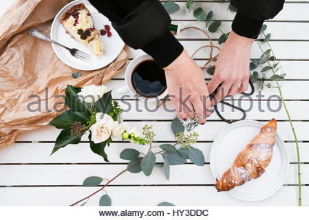 Sweden, Woman´s hands arranging food and flowers on white table - Stock Photo