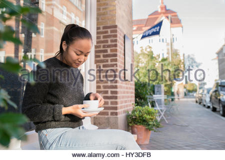 Sweden, Skane, Malmo, Woman sitting and holding cafe cup - Stock Photo