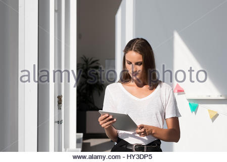 Sweden, Businesswoman standing and using tablet - Stock Photo
