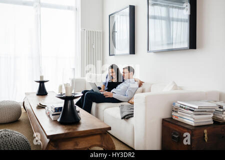 Germany, Man and woman sitting on sofa with laptop - Stock Photo
