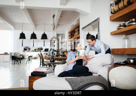 Germany, Mature couple talking in living room - Stock Photo