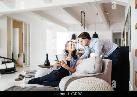 Germany, Woman sitting on sofa and smiling to man - Stock Photo