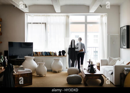 Germany, Couple looking through window in living room - Stock Photo