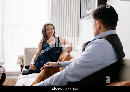 Germany, Couple sitting on sofa - Stock Photo