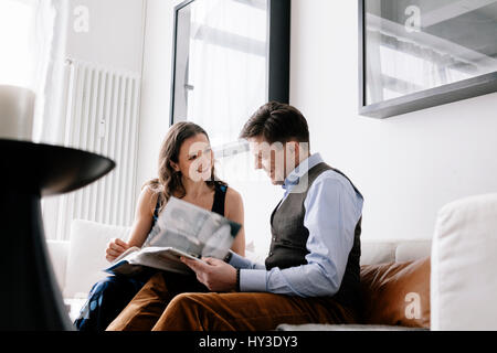Germany, Couple sitting on sofa and reading book - Stock Photo