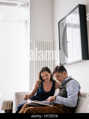 Germany, Couple sitting on sofa an reading book - Stock Photo