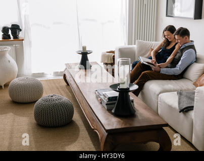 Germany, Couple sitting on sofa in living room - Stock Photo