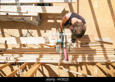 Sweden, Sodermanland, Overhead view of carpenter cutting wooden plank with circular saw - Stock Photo