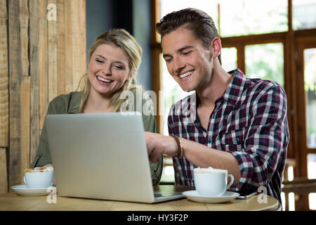 Cheerful young couple using laptop at table in coffee shop - Stock Photo