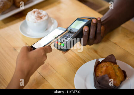 Cropped image of barista accepting payment through mobile phone at cafe - Stock Photo