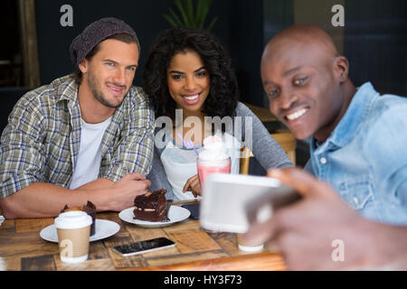 Happy young man with friends taking selfie at wooden table in coffee shop - Stock Photo