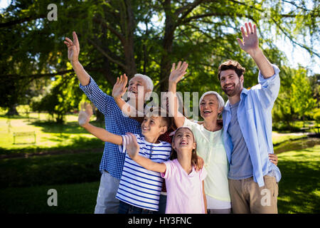 Happy multi generation family waving hand in air at the park - Stock Photo