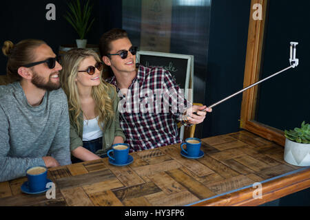 Happy friends taking selfie with monopod at table in cafeteria - Stock Photo