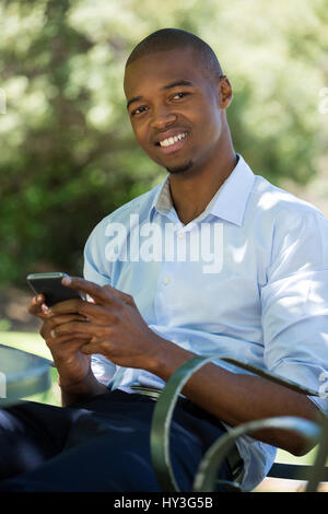 Portrait of happy young man using mobile phone at outdoor restaurant - Stock Photo