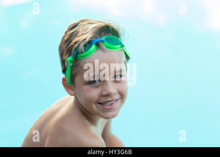 Portrait of smiling little boy wearing green swimming goggles - Stock Photo