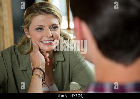 Romantic young man touching womans face in coffee shop - Stock Photo