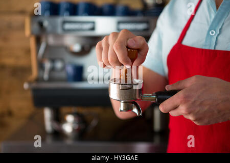 Midsection of male barista using tamper to press ground coffee into portafilter in cafe - Stock Photo