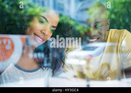 Smiling young couple in coffee shop seen through window - Stock Photo