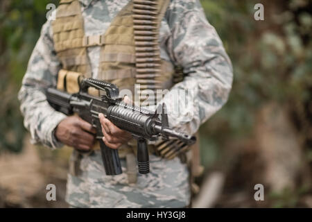Mid section of military soldier holding a rifle in boot camp - Stock Photo