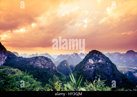 Sunset over karst landscape by Yangshuo in China - Stock Photo