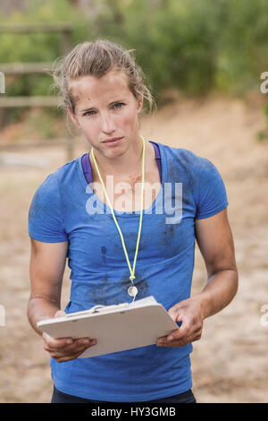 Portrait of female trainer holding clipboard during obstacle course in boot camp - Stock Photo