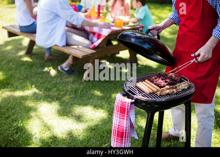 Mid section of man barbequing in the park - Stock Photo