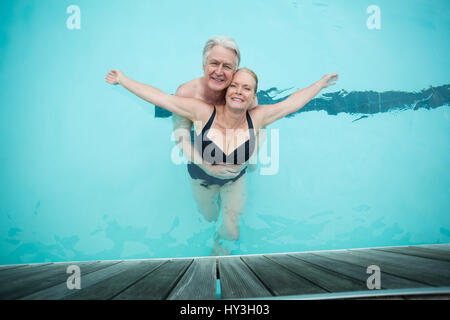 Overhead view of mature couple swimming in pool - Stock Photo