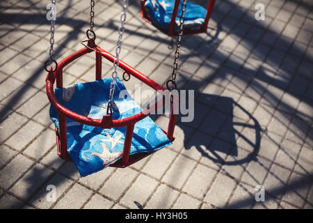 Red carousel seats, during spring sunny day. - Stock Photo