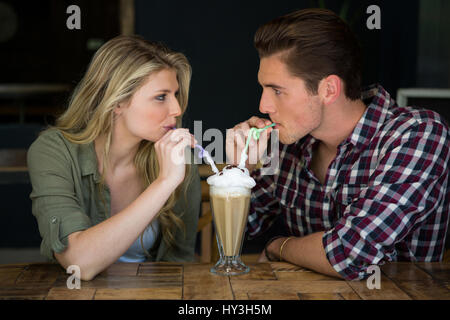 Loving young couple having milkshake at table in coffee shop - Stock Photo