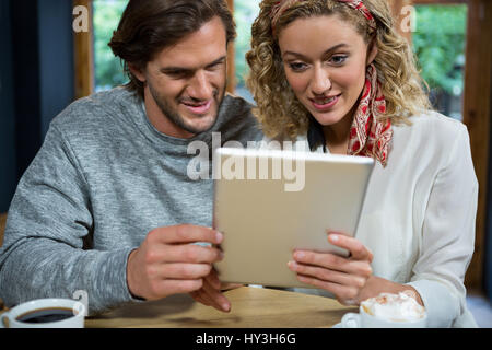Loving young couple using tablet computer at table in cafeteria - Stock Photo
