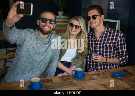 Happy man with friends taking selfie at table in coffee shop - Stock Photo