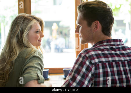 Loving young couple looking at each other in coffee house - Stock Photo