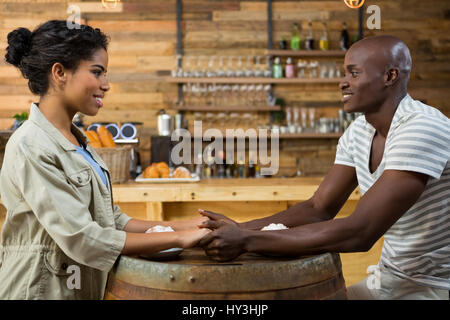Side view of loving young couple holding hands at table in coffee house - Stock Photo