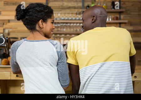 Rear view of young couple looking at each other in coffee shop - Stock Photo