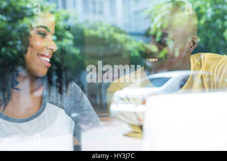 Loving young couple looking at each other in coffee house seen through window - Stock Photo