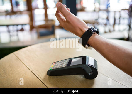 Cropped image of man hand using smart watch to express pay in coffee shop - Stock Photo