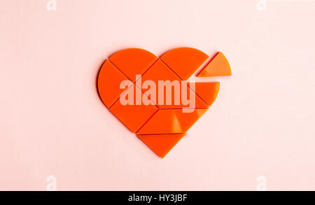Plastic puzzle in the form of heart with disconnected piece on a pink background - Stock Photo