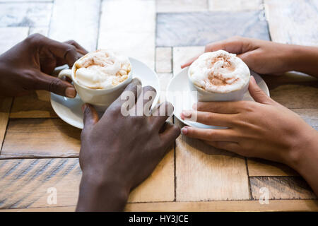 High angle close-up of multi ethnic couple hands holding coffee cups in cafe